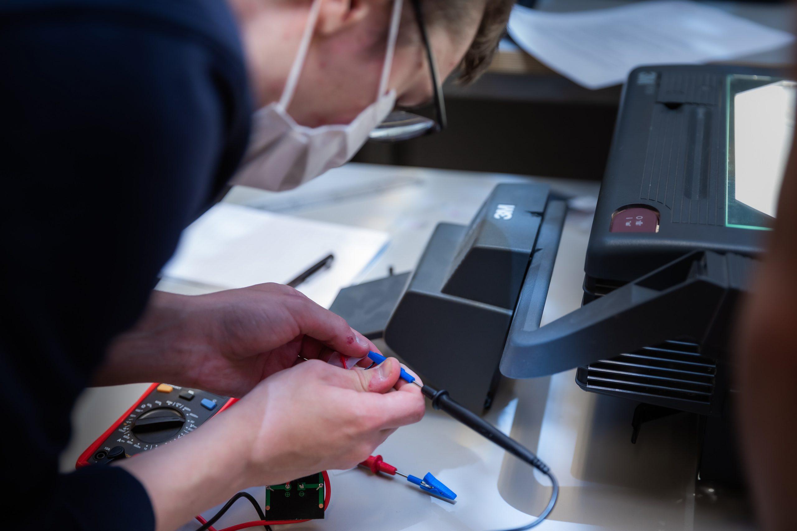 1. vuosikurssin opiskelijoita pienryhmissä materiaalitekniikan laboratoriossa tutkimassa kidevirheiden vaikutusta piiaurinkokennon toimintaan.
